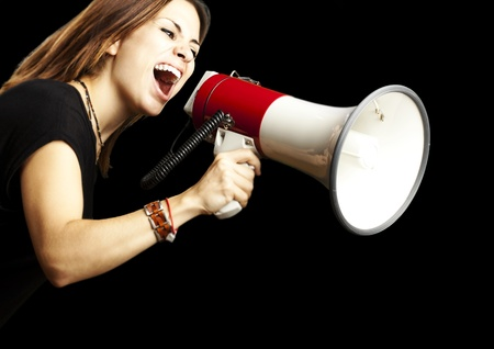 portrait of young girl shouting with megaphone over black background Stock Photo - 13156219