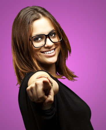 portrait of young woman pointing with glasses over purple background Stock Photo - 13156231