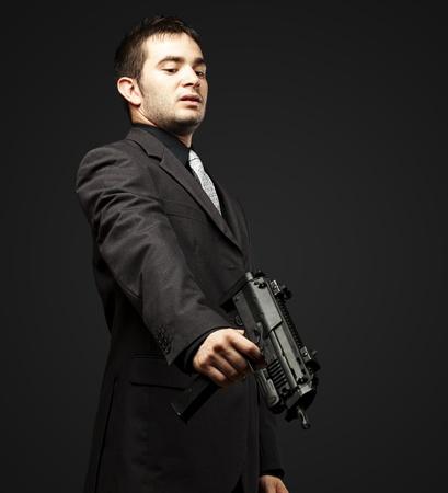mafia man aiming down with gun against a black background