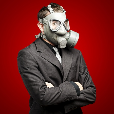 protective suit: portrait of a business man with gas mask over red background