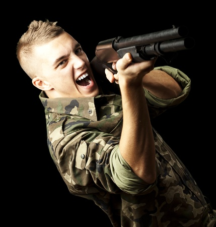 portrait of a young soldier aiming with shotgun against a black background Stock Photo - 13156350