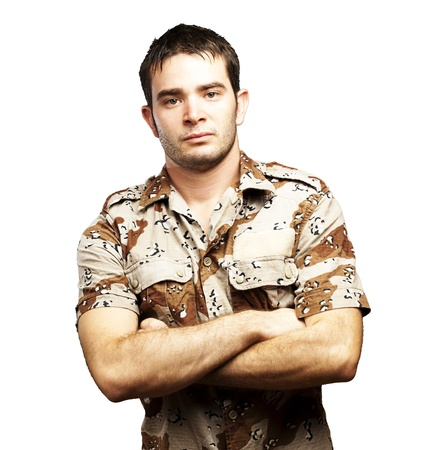 iraq war: portrait of a serious young soldier standing against a white background