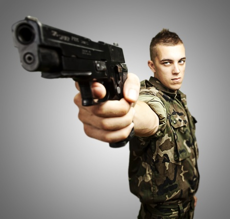portrait of caucasian soldier with jungle camouflage pointing with pistol over grey background photo