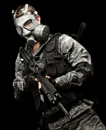 portrait of young soldier with gas mask and rifle against a black background Stock Photo - 13071361