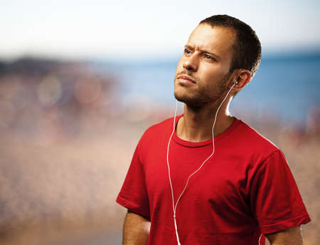 young man listen to music near the beach photo