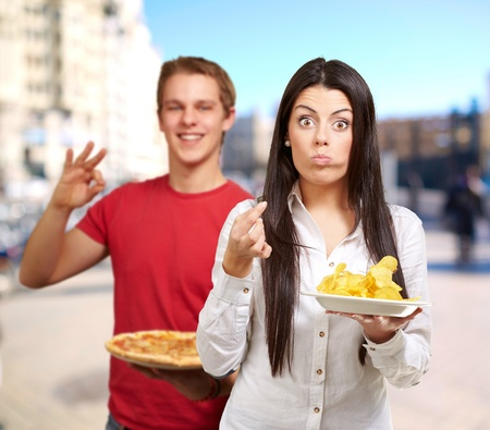 portrait of young friends holding pizza and potato chips at street photo
