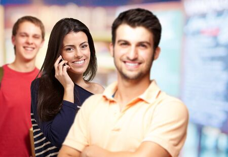 young friends smiling and one girl talking on mobile over abstract background photo