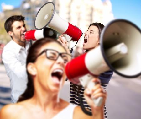 hombre megafono: j�venes amigos con meg�fono gritando contra un edificio Foto de archivo