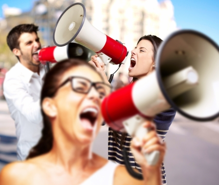 loudspeaker: young friends screaming with megaphone against a building