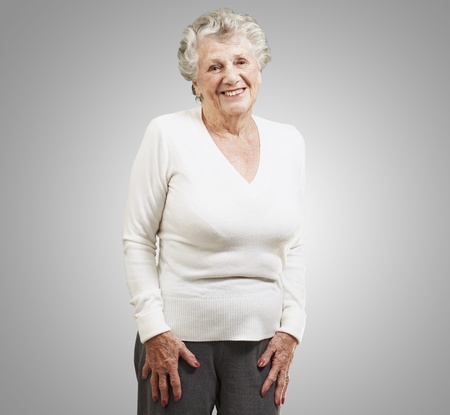 pretty senior woman smiling against a grey background photo