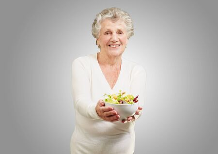portrait of senior woman showing a fresh salad over grey background photo