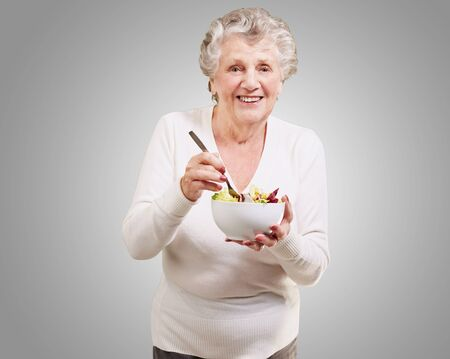 old people eating: portrait of senior woman eating salad over grey background Stock Photo