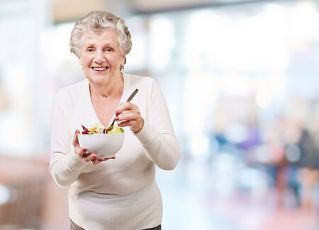 portrait of senior woman eating salad indoor photo