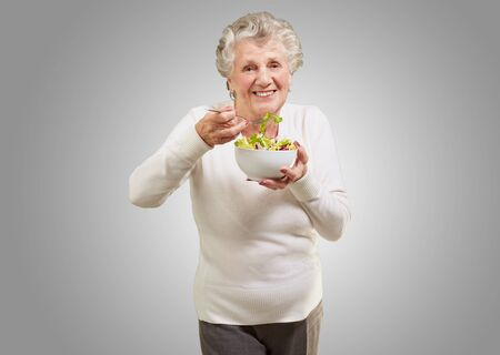 portrait of senior woman eating a fresh salad over grey background photo