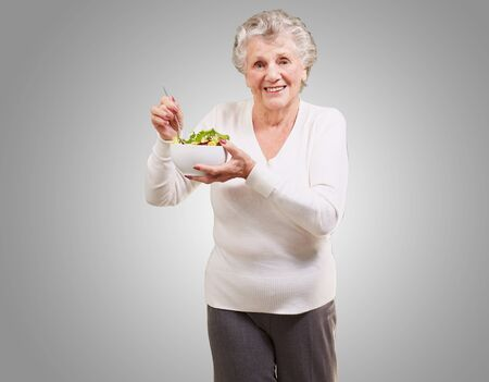 portrait of senior woman eating salad over grey background photo