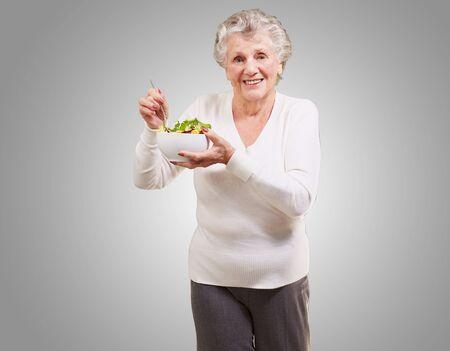portrait of senior woman eating salad over grey background photo