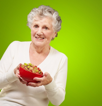 portrait of healthy senior woman holding cereals bowl over green background photo