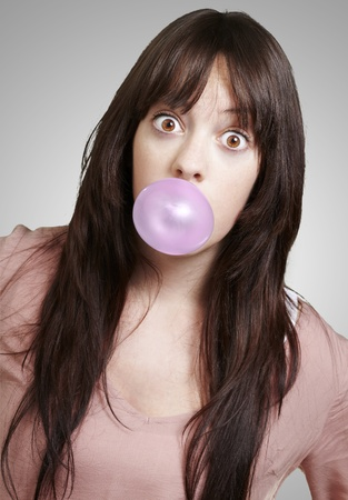 bubblegum: young girl with a pink bubble of chewing gum against a grey background Stock Photo