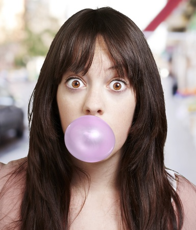 young girl with a pink bubble of chewing gum against a street background photo
