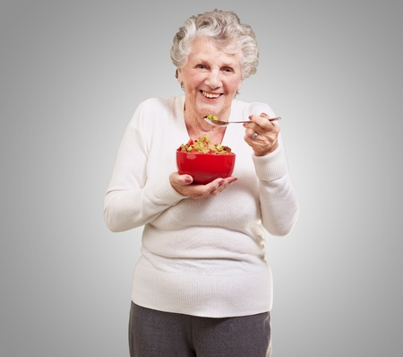 old people eating: portrait of senior woman holding a cereals bowl against a grey background Stock Photo