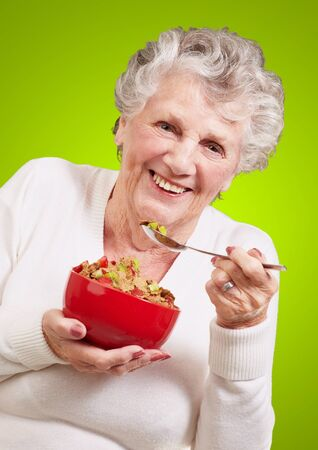 portrait of senior woman holding a cereals bowl against a green background photo