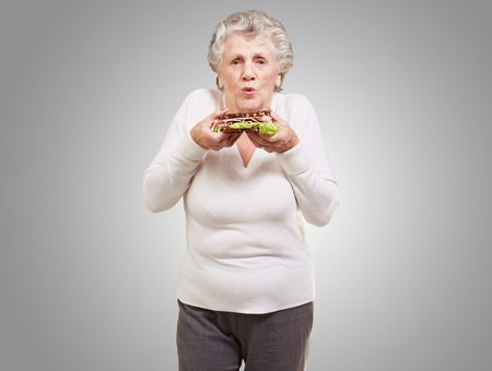 portrait of senior woman holding a delicious sandwich over grey background photo