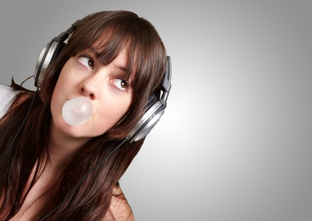 portrait of young woman listening to music with bubble gum over grey background Stock Photo - 13280484
