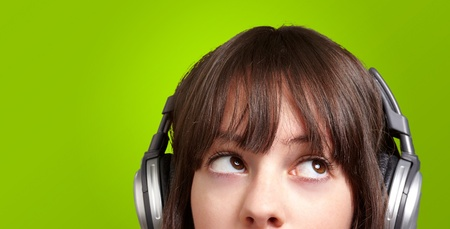 portrait of young woman listening to music over green photo