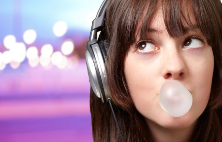portrait of young woman listening to music with bubble gum over abstract lights photo