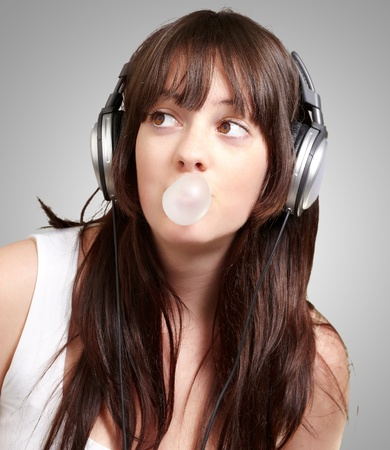 sexy headphones: portrait of young woman listening to music with bubble gum over grey background