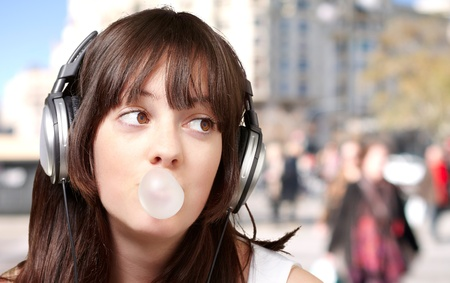 portrait of young woman listening to music with bubble gum at crowded street photo