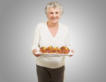 portrait of senior woman showing homemade muffins over grey photo