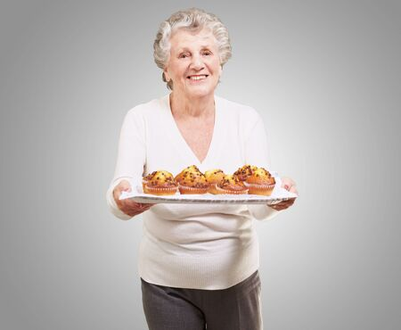 portrait of senior woman showing a chocolate muffin tray over grey background photo
