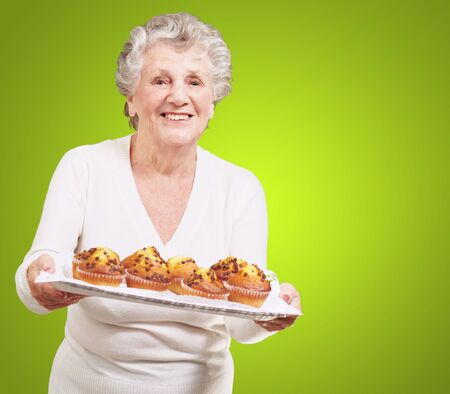 portrait of senior woman showing a chocolate muffin tray over green background photo