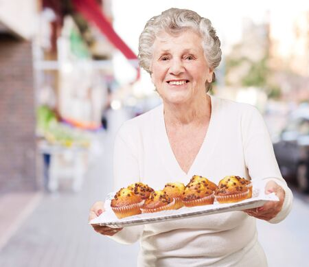 bakery store: portrait of senior woman showing a chocolate muffin tray at street