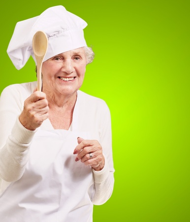 portrait of senior cook woman holding a wooden spoon over green background photo
