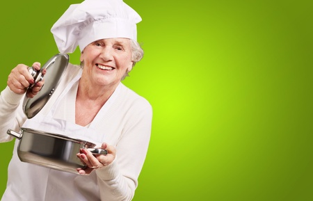 portrait of cook senior woman opening sauce pan over green photo