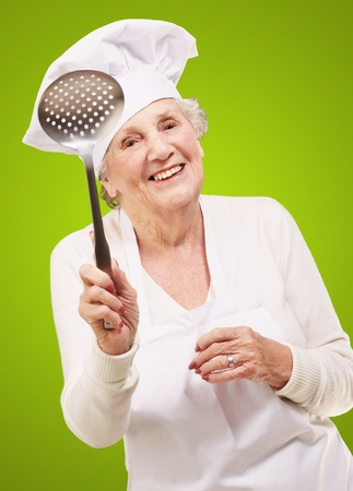 portrait of sweet senior cook woman holding a metal spoon over green photo