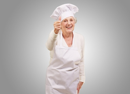 portrait of cook senior woman doing approval gesture over grey background Stock Photo - 13280523