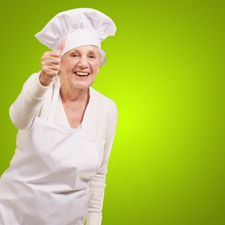 portrait of cook senior woman doing approval gesture over green background Stock Photo - 13280501