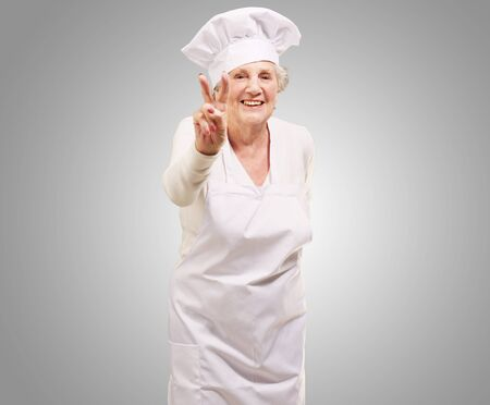 portrait of cook senior woman doing approval gesture over grey background photo