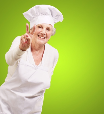 portrait of cook senior woman doing approval gesture over green background photo