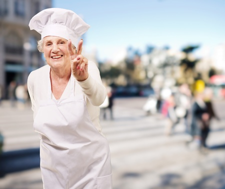 portrait of cook senior woman doing good gesture at crowded street photo