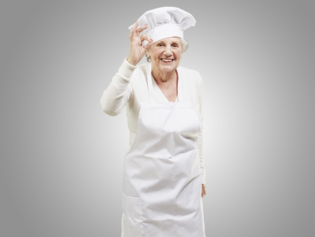 senior woman cook doing an excellent symbol against a grey background photo