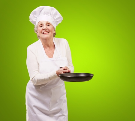 portrait of a friendly cook senior woman holding pan over green background photo