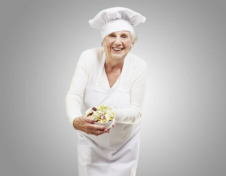 senior woman cook holding a bowl with salad against a grey background Stock Photo - 13280545