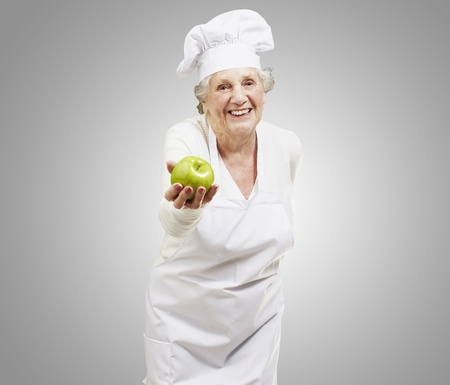 senior woman cook offering a green apple against a grey background photo