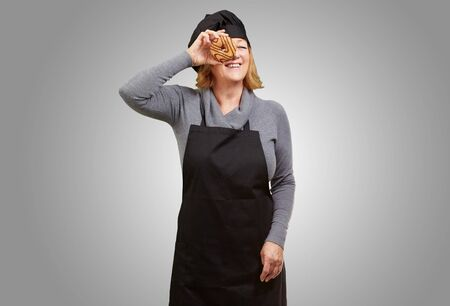 Middle aged cook woman looking through a donut over grey background photo