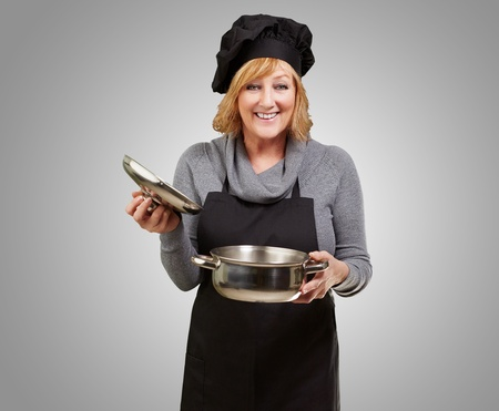Middle aged cook woman holding a souce pan over grey background photo