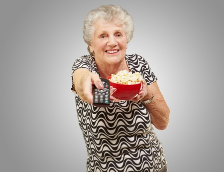 portrait of senior woman holding pop corn bowl and changing channel of tv over grey background photo